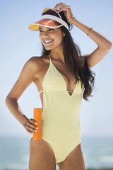 Beautiful woman holding a suntan lotion on the beach