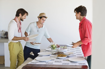 Friends arranging food on a dining table