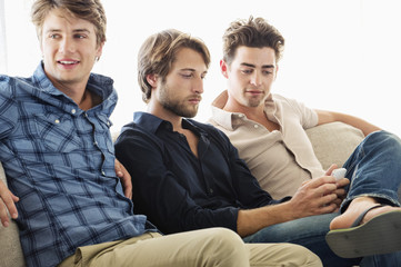 Three male friends sitting together on a couch