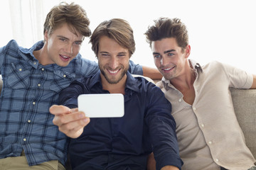 Three friends sitting on a couch and looking at mobile phone