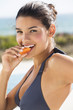 Beautiful woman eating a slice of papaya