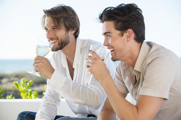 Two male friends enjoying white wine in outdoor