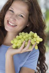 Portrait of a woman holding a bunch of grapes and smiling