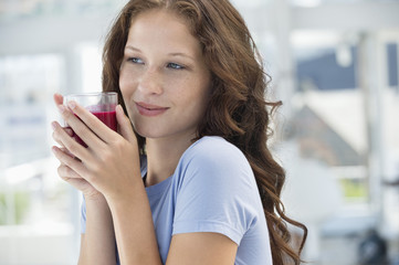 Woman holding a glass of pomegranate juice