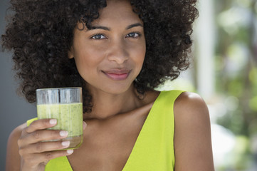 Portrait of a woman holding a glass of kiwi juice