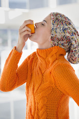 Woman squeezing juice from an orange into her mouth