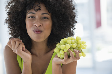 Portrait of a woman eating grapes