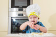 Child baking cupcakes in kitchen at home