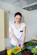 Smiling woman preparing fresh meal in kitchen
