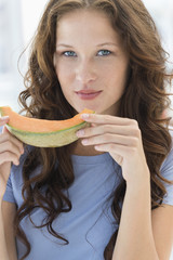 Portrait of a woman eating melon