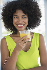 Portrait of a smiling woman holding a glass of mango shake