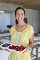 Woman holding a tray of assorted berries and smiling at home