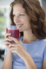 Smiling woman holding a glass of pomegranate juice