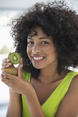 Portrait of a smiling woman showing kiwi fruits