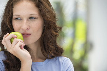 Close-up of a woman eating a green apple