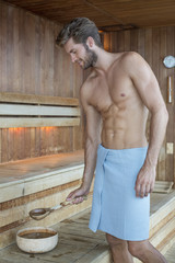 Man taking water from a bowl in a sauna