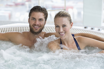 Portrait of a smiling couple in a hot tub
