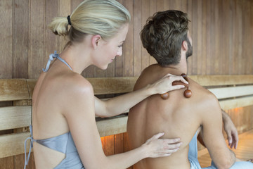 Woman massaging on her friend's back with a massager in a sauna