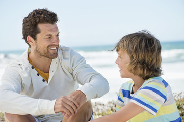 Man sitting with his son on the beach