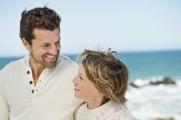 Man with his son smiling on the beach