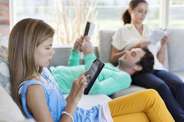 Girl using a digital tablet with her parents reading books at home