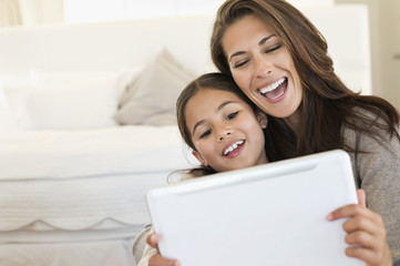 Woman and her daughter looking at a digital tablet