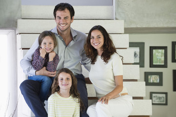 Family sitting on steps and smiling