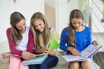 Three girls sitting on stairs and studying in a school