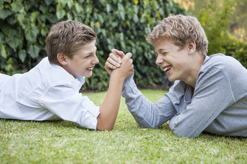 Two boys arm wrestling on grass