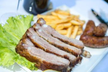 Costine e salsicce alla griglia con patatine fritte