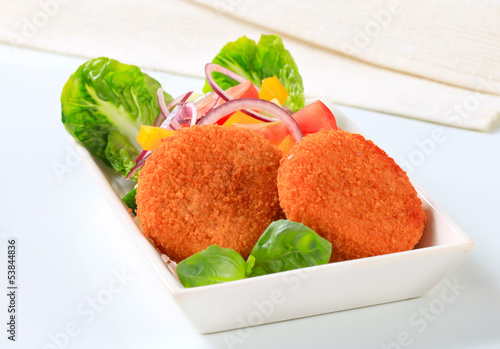 Fried cheese or fish cakes with fresh vegetables