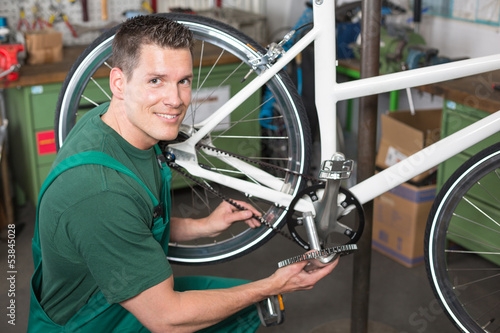 Bicycle mechanic repairing tooth belt in a workshop
