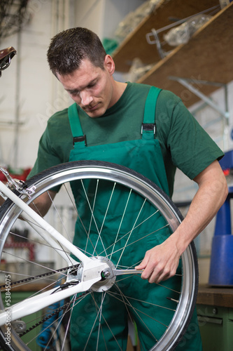 Mechanic repairing wheel on a bicycle in workshop