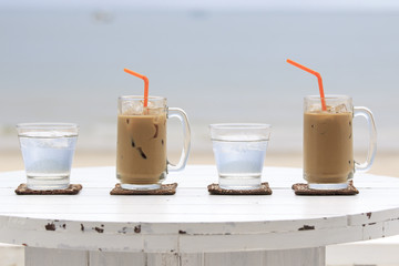 Iced coffee with straw and glass of water
