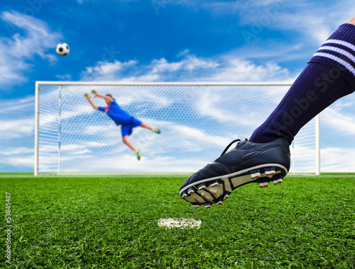 foot shooting soccer ball out of goal