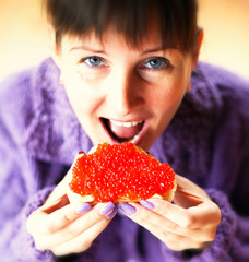 Woman eating the sandwich with red caviar