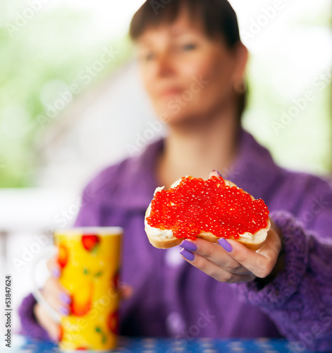 woman with red caviar sandwich