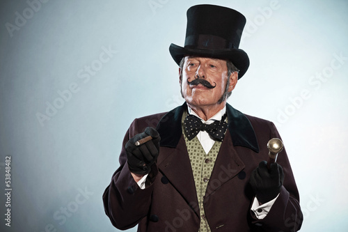 Vintage dickens style man with mustache and hat. Smoking cigar.