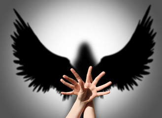 Angel, hand shadow like wings of darkness
