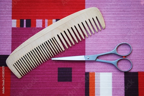 Professional scissors and wooden comb on colorful background