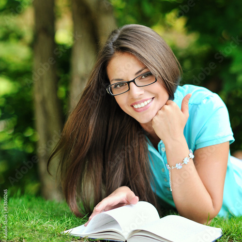Young beautiful girl reading book in a summer green park