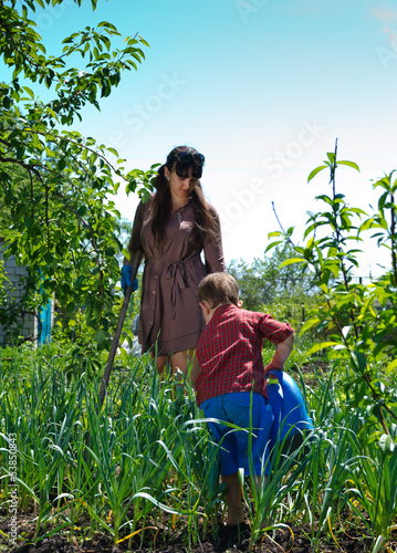Small boy gardening with his mother