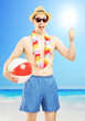 Smiling male in swimming shorts, holding a beach ball and giving
