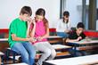 Teenage Schoolchildren Listening Music In Classroom
