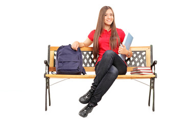 Smiling female student sitting on a wooden bench and holding a n