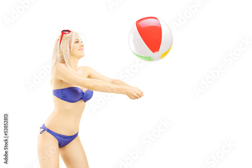 Young woman in bikini playing with a beach ball