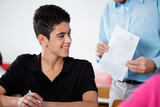 Fototapety Professor Holding Paper With Teenage Boy At Desk