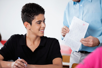 Professor Holding Paper With Teenage Boy At Desk