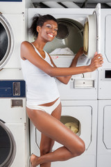 Woman Standing By Dryer In Laundry