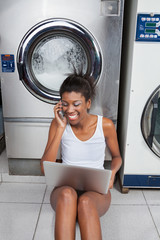 Woman Using Laptop And Mobilephone In Laundry